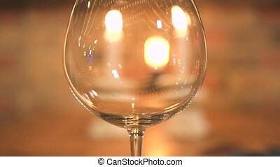 Empty wineglass on burning candles background. Close up wine glass on evening dinner table with candles.