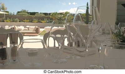 Empty wineglasses on dining table. Bouquet on white...
