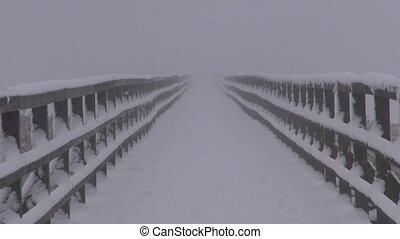 empty winter wooden snowy bridge and morning fog