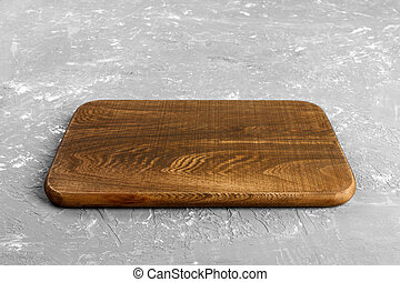 Empty wood cutting board on gray background with copy space. Perspective view