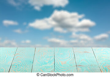 Empty wooden backdrop of blue color on a background of blurred sky.