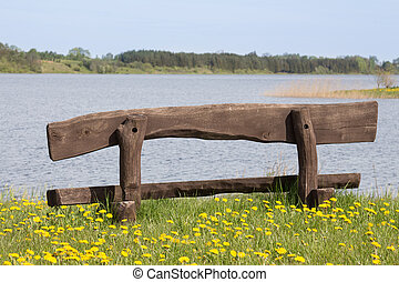 Empty wooden bench at the lake shore