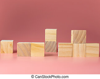 Empty wooden cube on a pink background. For new ideas to be put into the picture.Rear focus.