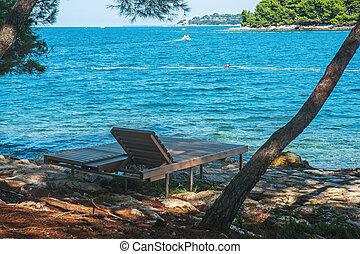 Empty wooden deck chair on a beautiful European beach