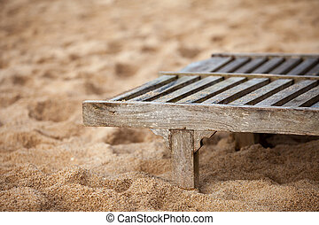 Empty wooden deck chair on the beach