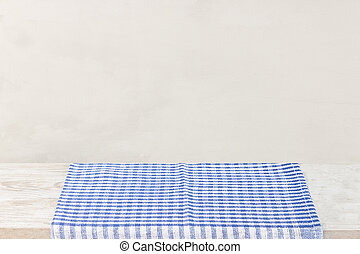 Empty wooden desk table and red checked tablecloth over gray wallpaper background