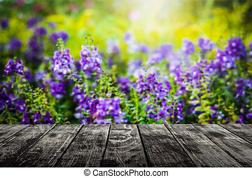 Empty wooden floor with blurred flower in the meadow under sunlight background.