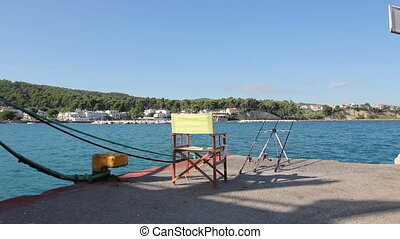 Empty wooden folding chair on pier with few fishing rods -...