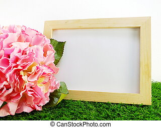 empty wooden frame with flower on green background