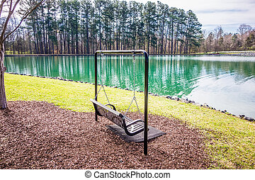 Empty wooden park bench overlooking a lake or pond