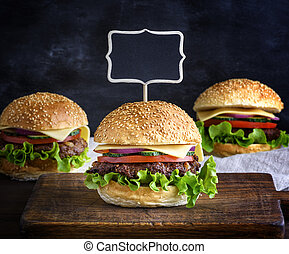 large hamburger with a meatball and vegetables
