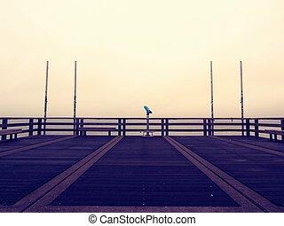 Empty wooden sea bridge. The way to see the sunrise above sea horizon, texture selective focus