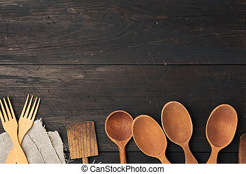 empty wooden spoons, forks and spatulas on a brown wooden background from boards