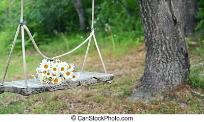 Empty wooden swing, hanging by rope, with daisies bouquet on...
