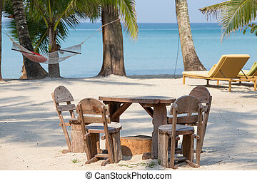 Empty wooden table and chairs of a beach tropical garden near the sea