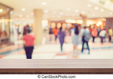 Empty wooden table for product display or montage and blurred shopping mall background.