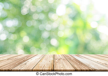 Empty wooden table top with blurred green garden background.
