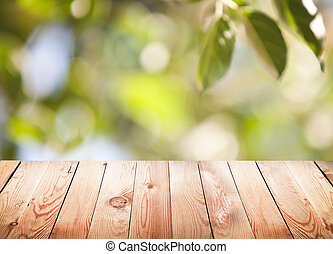 Empty wooden table with foliage bokeh background.