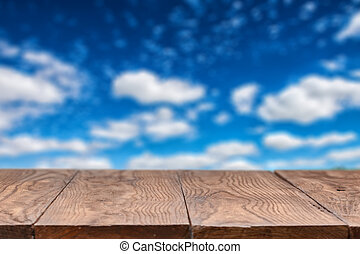 Empty wooden table with sky on background