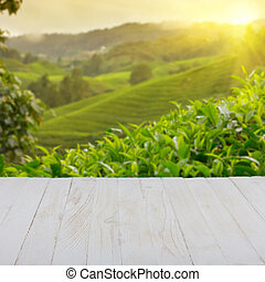 Empty wooden table with tea plantation on background, blank ...