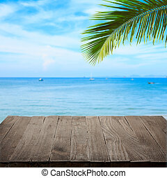 Empty wooden table with tropical sea and palm leaf on background, blank place for product