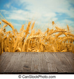 Empty wooden table with wheat field on background, blank...