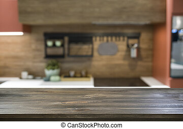 Empty wooden tabletop and defocused modern kitchen as background for design. Copy space. Blurred interior.