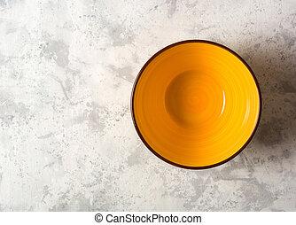 Empty yellow ceramic bowl on a light stone background.