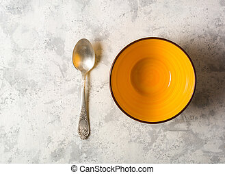 Empty yellow ceramic bowl on a light stone background. Silver spoon near.
