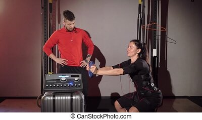 EMS electro stimulation sports equipment in gym. Trainer and...