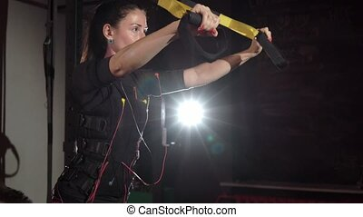 EMS electro stimulation sports equipment in gym. Woman doing...