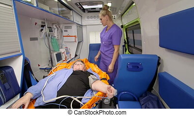 EMT professional provide emergency medical care for senior patient in ambulance