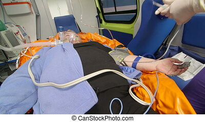 EMT provide emergency medical care to patient in ambulance intravenous infusion