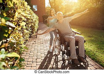 en, äldre bemanna, är, sittande, in, a, wheelchair., den, flicka, rolls, den, och, de, dumbom, around., de, gå, utanför, och, laugh.