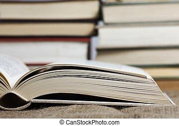 en öppen bok, med, suddig, böcker, in, den, bakgrund