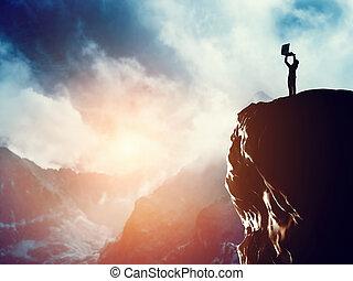en, mand stå, hos, laptop, på, den, højdepunkt, i, en, bjerg, hos, solnedgang