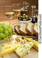 en, platter, i, middelhavet mad, heriblandt, ost, druer, hvid vin, bread, olivener, oliven olie, og, balsamic, vinegar., skud, ind, smukke, varm, lys, hos, brændvidden, på, den, ost, ind, den, forgrund.