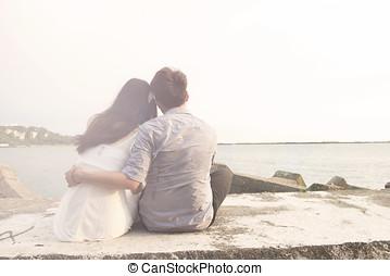 en, ungt par, sidde stranden