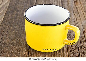 Enamel yellow mug on wooden background