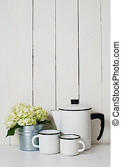 Enameled kitchenware, vintage coffee pot and cups, and white...