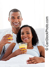 Enamored couple drinking lying on their bed
