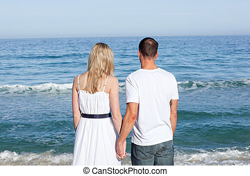 Enamored couple holding hands at the shore line at the beach