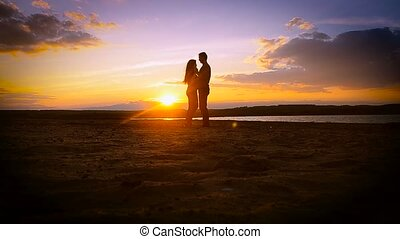 enamored girl and the guy on the beach embracing at sunset