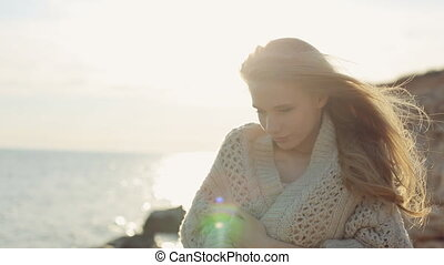 Enamored girl with long hair wearing a cream knitted cardigan stands near the sea at sunset