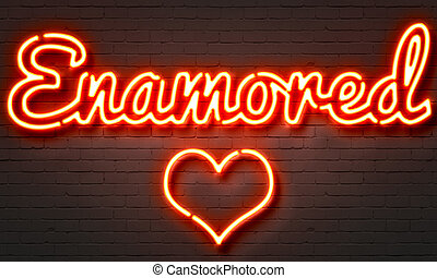 Enamored neon sign on brick wall background.