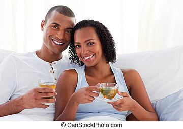 enamoured, coppia, bere, uno, tazza tè, su, loro, letto