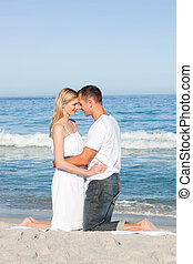 Enamoured couple kissing at the shore line. Love concept.