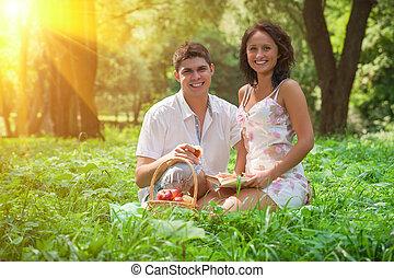 enamoured, młoda para, odprężając, w parku, jedzenie, jabłka