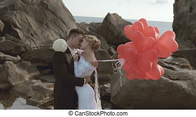 Enamoured newlyweds stand with balloons in the form of heart in the rocks by the sea