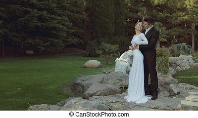 Enamoured newlyweds standing among green park - Enamoured...